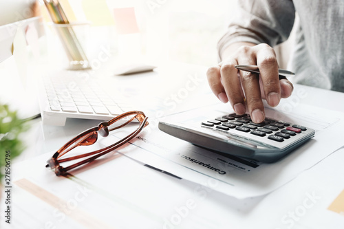 obraz lub plakat Close up of businessman or accountant hand holding pencil working on calculator to calculate financial data report, accountancy document and laptop computer at office, business concept