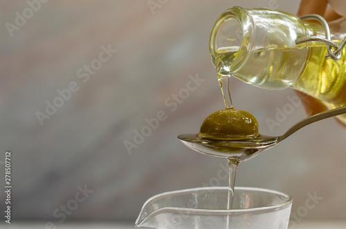 Spoed Fotobehang Aromatische Pouring Olive oil in to spoon.