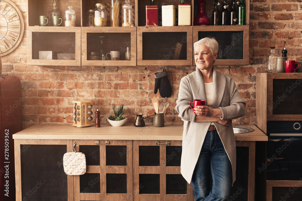 Fototapeta Dreamy senior woman enjoying coffee at kitchen