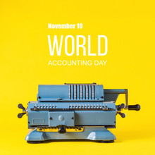 Old Calculating Machine On Yellow Background. Word Accounting Day  Concept