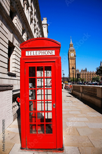 Photo  Iconic Red Telephone Booth and Big Ben Clock Tower over blue sky.