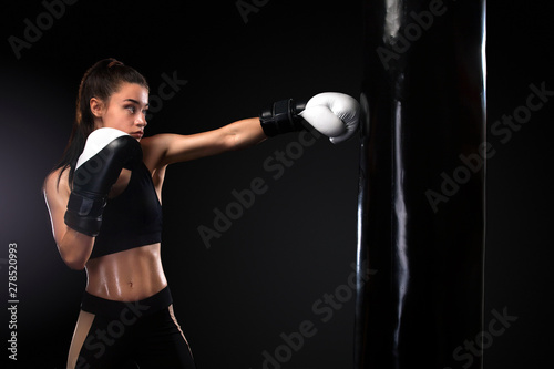 Obraz na plátne Woman boxer fighting in gloves with boxing punching bag on black background