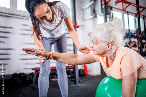 Foto  Senior woman with trainer doing rehab using pilates ball in the rehabilitation c