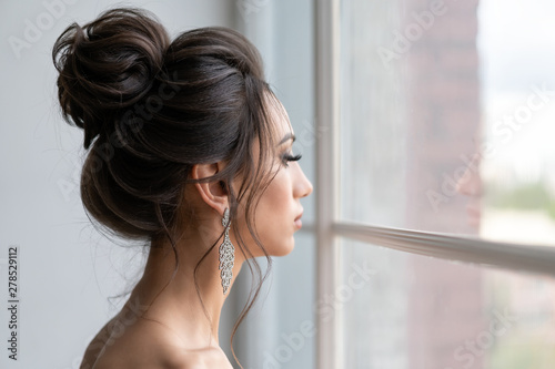 Fototapeta beautiful girl with hairstyle high beam looks out window. Evening image girl. obraz
