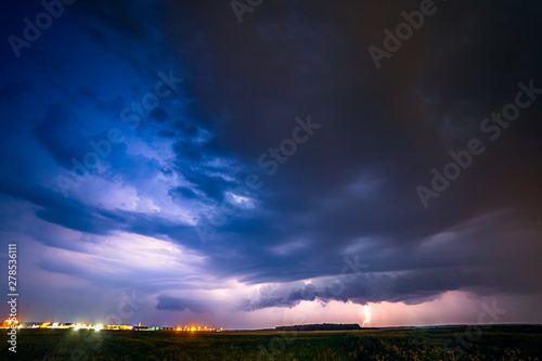 Valokuva  A severe thunderstorm is illuminated by a lightning bolt at night in Lithuania