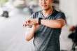Leinwandbild Motiv Male in gray T-shirt checking fitness tracker while standing on blurred background of city street during outdoor workout