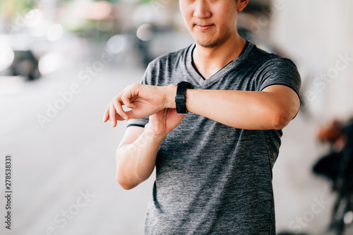 plakat Male in gray T-shirt checking fitness tracker while standing on blurred background of city street during outdoor workout
