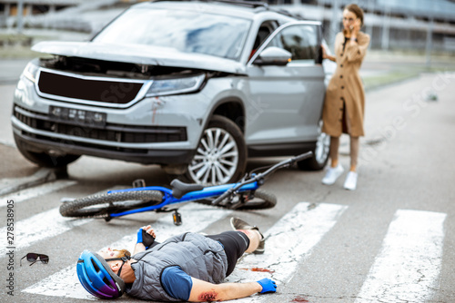 Fotografía Road accident with injured cyclist lying on the pedestrian crossing near the bro