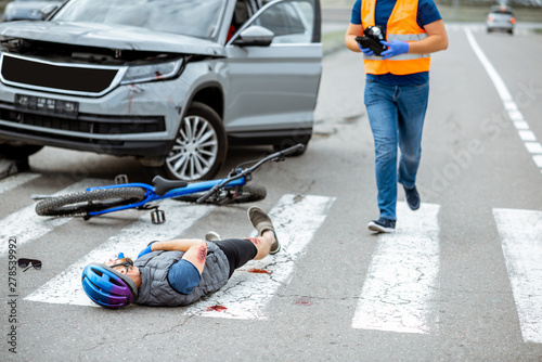 Fotografie, Obraz  Road accident with injured cyclist lying on the pedestrian crossing near the bro