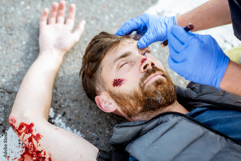 Fototapety, obrazy: Medic checking unconscious person with flashlight, applying first aid to the bleeding person on the road after the accident on the pedestrian crossing