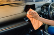 Hand with microfiber cloth cleaning car interior.