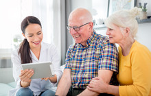 Nurse Showing Medical Raport Using Tablet To Senior Couple At Home