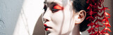 portrait of beautiful geisha with red and white makeup in sunlight with shadows, panoramic shot