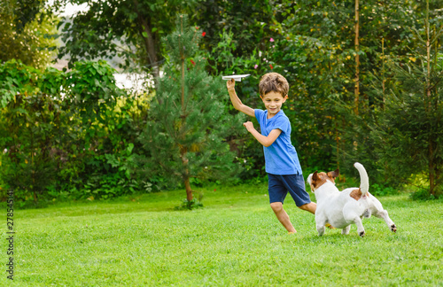 Fotografie, Tablou Kid playing with paper airplane and dog outdoors at backyard lawn