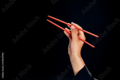 cropped view of woman holding chopsticks isolated on black
