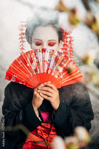 selective focus of geisha in black kimono with flowers in hair holding hand fan and sakura branches in smoke