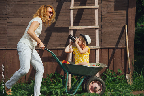 Fotografía  Mother driving a wheelbarrow, while her daughter with camera riding in it