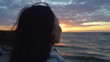 Portrait of asian woman looking at the sunset over the sea. View from back.