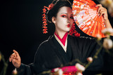 selective focus of geisha in black kimono with red flowers in hair holding hand fan and sakura branches isolated on black