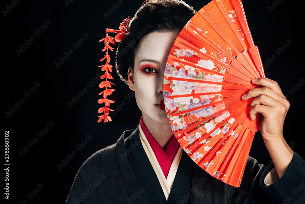 Fototapeta attractive geisha in black kimono with flowers in hair holding bright hand fan isolated on black