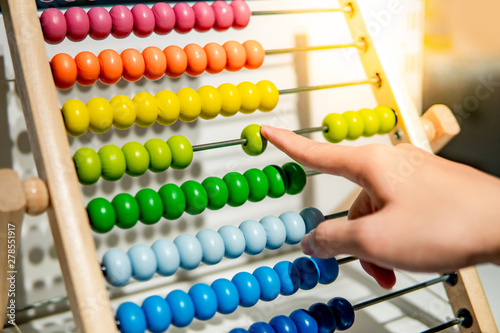 Valokuva Male hand calculating with beads on wooden rainbow abacus for number calculation