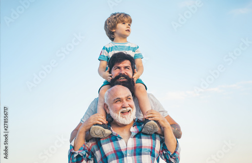 Men generation: grandfather father and grandson are hugging looking at camera and smiling Tableau sur Toile