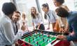 Leinwandbild Motiv Coworkers playing table football on break from work