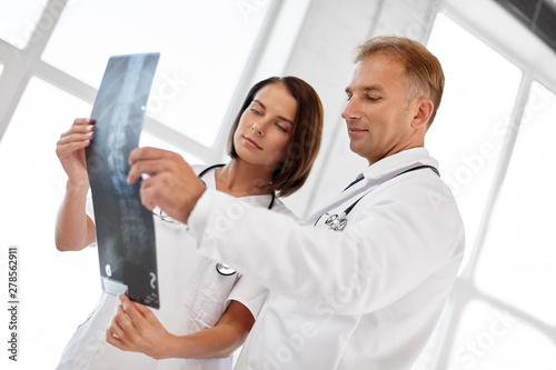 healthcare, medicine and surgery concept - male and female doctors with x-ray of spine at hospital