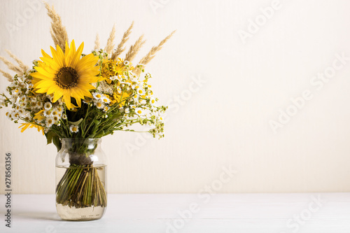 Field flowers in a glass vase. Summer bouquet of flowers on the white background - 278563356