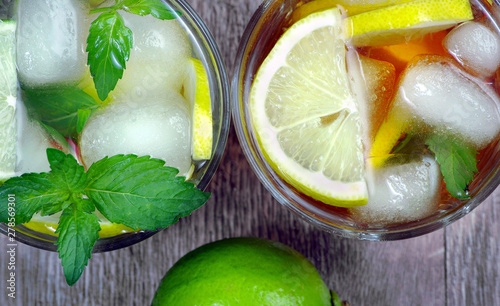 Poster de jardin Bar glass of refreshing drink. glass of cold water with ice, mint and lemon on a wooden table. top view