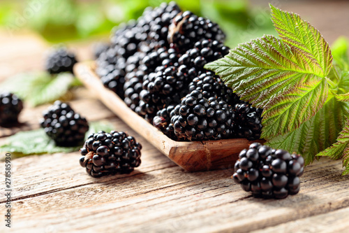 Ripe juicy blackberries with leaves on a wooden table. Wallpaper Mural