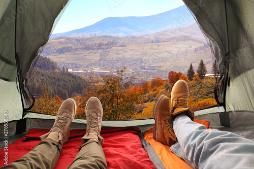 Obraz Closeup of people in camping tent with sleeping bags on mountain hill, view from inside - fototapety do salonu