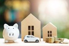 Piggy Bank, Little Toy Car, Money Coins Stacked On Each Other In Different Positions, House In Paper Model On The Wooden Table. Credit Financial Growing Loan To Buy Real Asset Concept. Saving Money