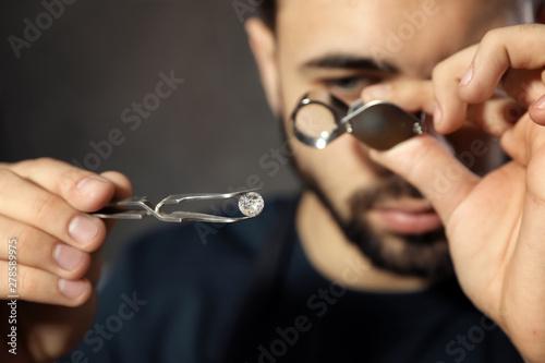 Male jeweler evaluating precious gemstone in workshop, closeup Wallpaper Mural