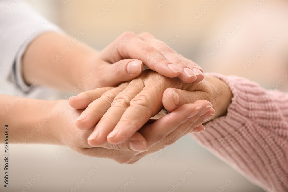 Fototapeta Nurse holding hands of elderly woman against blurred background, closeup. Assisting senior generation