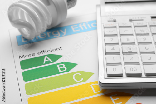 Fotografía Energy efficiency rating chart, fluorescent light bulb and calculator, closeup
