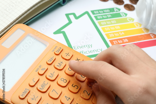 Fotografiet Woman with calculator and energy efficiency rating chart at table, closeup