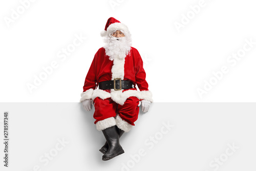 Fototapeta Santa claus sitting on a white banner obraz