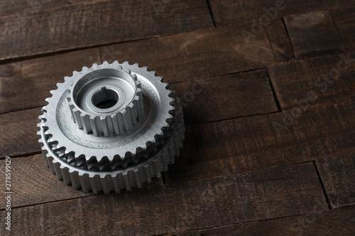 Three metal silver gears lies on old weathered wooden table in workshop Wallpaper Mural