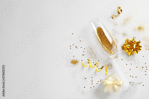 In de dag Alcohol Champagne glass with gold glitter, gift box and space for text on white background, top view. Hilarious celebration