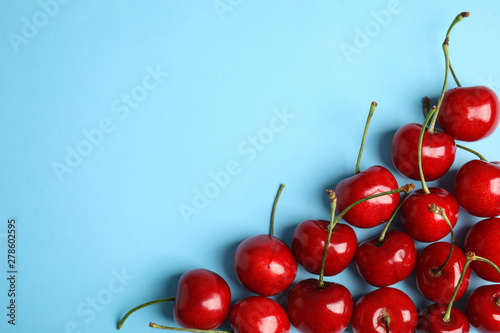 Canvas Composition with sweet cherries on light blue background, top view