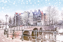 Traditional Dutch Old Houses And Bridges On The Canals In Amsterdam On A Snowy Winter Night, The Netherlands