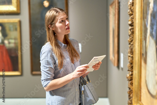 Fototapeta  Portrait of young woman with a guide looking at pictures at museum of arts