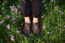 Low Section Of Woman Wearing Hiking Boots While Standing On Pink Flowe