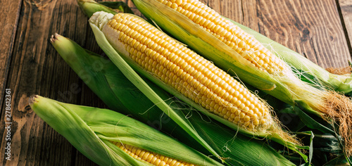 Fényképezés Fresh corn on the cob on a wooden background, long banner