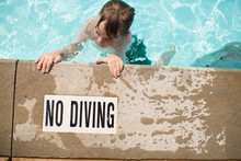 Overhead View Of Boy Swimming In Pool Next To No Diving Sign On Deck