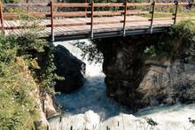 Mountain River With White Foam Heads Through Narrow Passage Between Rocks Under Wooden Bridge