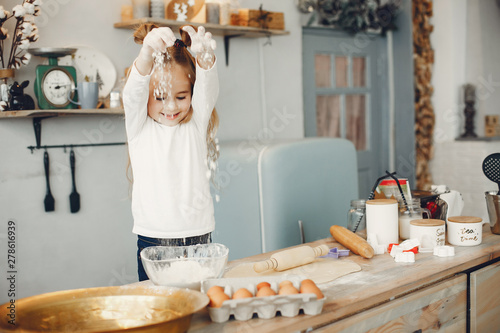 Fototapeta Child in a kitchen. Little girl with a dough.
