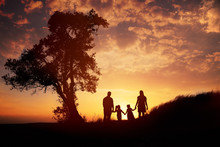 Happy Family Silhouette Standing On Against Sunset Time