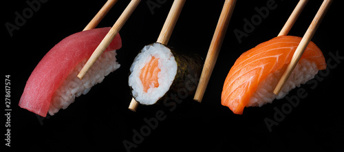 Traditional japanese sushi pieces placed between chopsticks, separated on black background